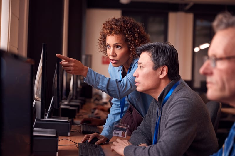 Black woman and Asian man working at a computer