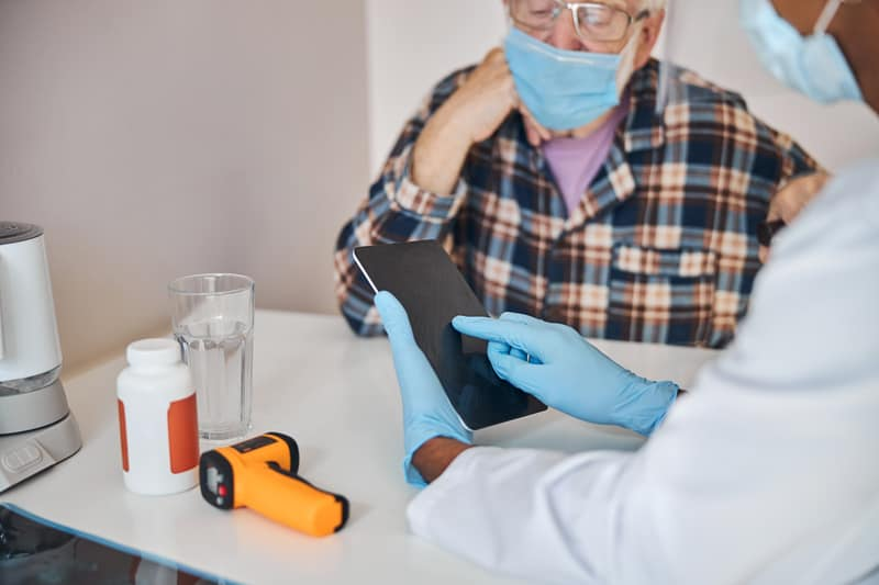 staff and patient with pandemic masks demonstrates benefits of blogs for senior service businesses