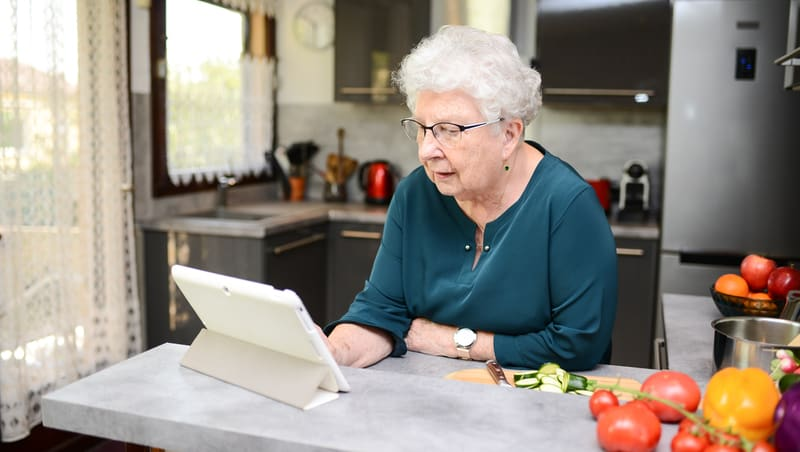Senior looking at tablet computer for article, Is digital advertising working for your senior business?